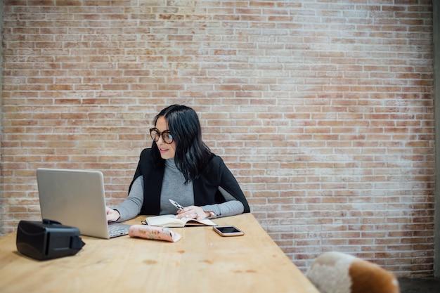 Jovem, mulher bonita, indoor, usando computador, sentando, trabalhando, escrivaninha Foto Premium