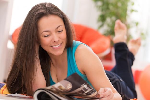 Jovem mulher bonita lendo em casa Foto gratuita