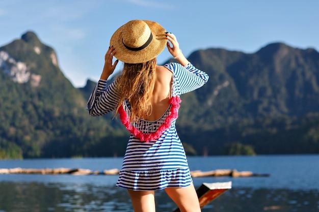 Jovem mulher bonita loira com cabelos longos, usando chapéu vintage e vestido da moda sexy brilhante parece para as montanhas e o lago, mostra a mão dela, incríveis aventuras de verão. Foto gratuita