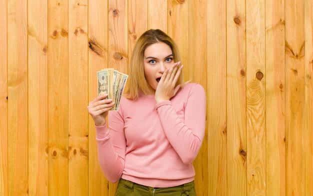 Jovem mulher bonita loira com notas de dólar na parede de madeira Foto Premium