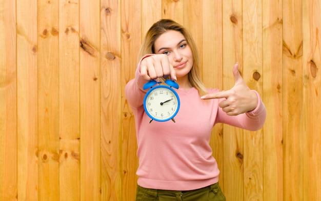 Jovem mulher bonita loira com um despertador na parede de madeira Foto Premium