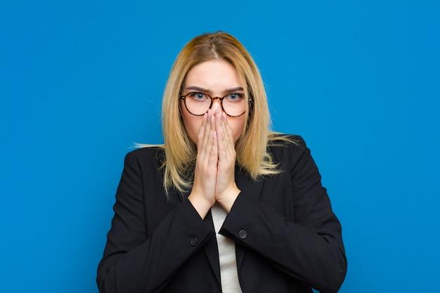 Jovem mulher bonita loira se sentindo preocupado, chateado e assustado, cobrindo a boca com as mãos, parecendo ansioso e tendo estragado a parede plana Foto Premium