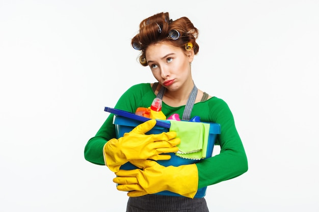 Jovem mulher bonita mantém ferramentas de limpeza com tristeza no rosto Foto gratuita
