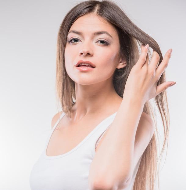 Jovem mulher bonita na parte superior da camiseta de alças que guarda a mão no cabelo. Foto Premium