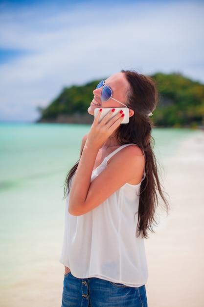 Jovem mulher bonita na praia falando por telefone Foto Premium