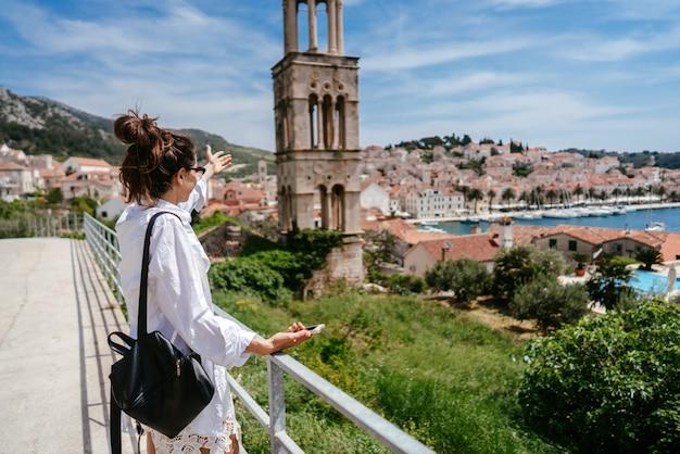 Jovem mulher bonita na varanda com vista para uma pequena cidade na croácia Foto gratuita