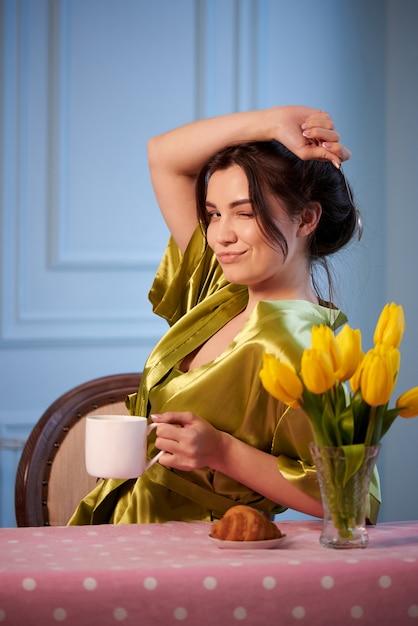 Jovem mulher bonita no café bebendo da manhã da roupa de noite com croissant. Foto Premium
