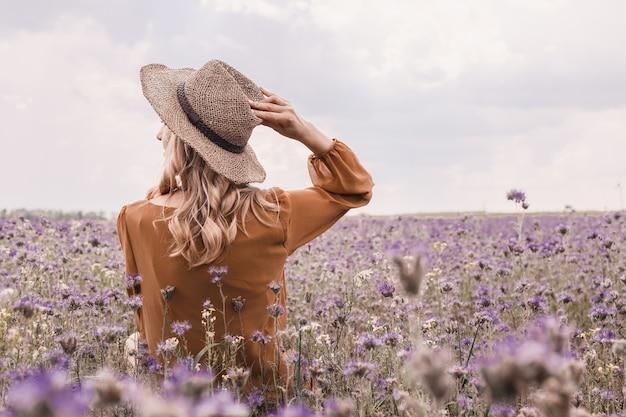 Jovem mulher bonita no chapéu no campo da alfazema. flores desabrochando Foto Premium