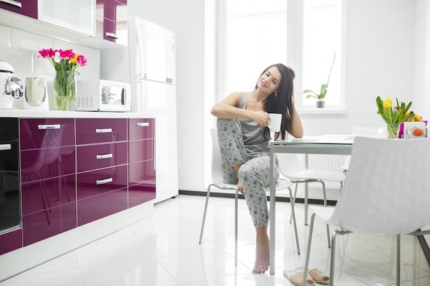 Jovem mulher bonita no início da manhã tomando café na cozinha. manhã fresca. bebida refrescante. senhora acordada. Foto Premium