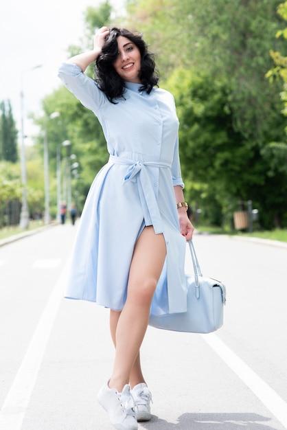 Jovem mulher bonita no vestido azul posando Foto gratuita