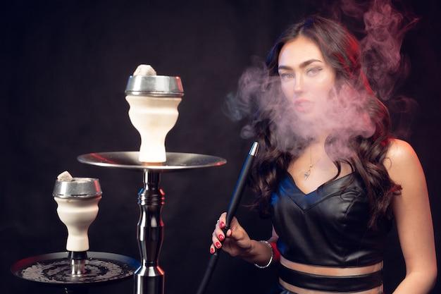 Jovem mulher bonita no vestido preto, fumar e exala o cachimbo de água Foto Premium