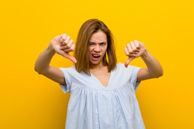 Jovem mulher bonita nova que mostra o polegar para baixo e que expressa o desagrado. Foto Premium