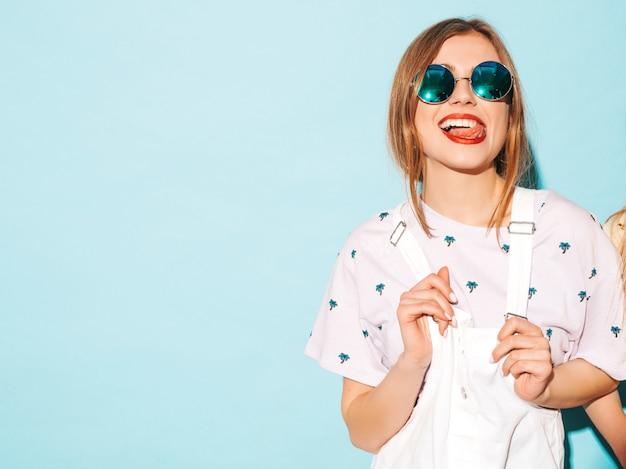 Jovem mulher bonita olhando. menina na moda em roupas de verão casual amarelo camiseta mostrando a língua em óculos de sol redondos. fêmea positiva mostra emoções faciais. modelo engraçado isolado em azul Foto gratuita