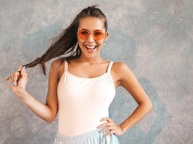Jovem mulher bonita olhando. menina na moda em verão casual vestido e óculos de sol. Foto gratuita