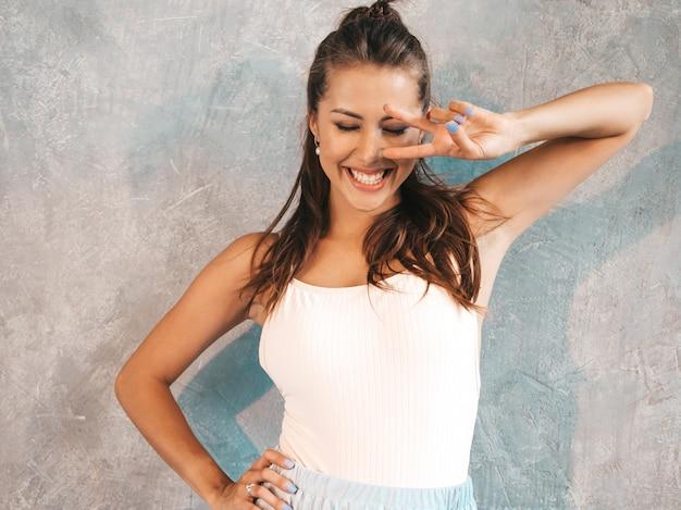 Jovem mulher bonita olhando. menina na moda em vestido de verão casual. .mostra o sinal de paz Foto gratuita