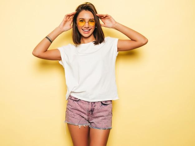 Jovem mulher bonita olhando para a câmera. menina na moda casual verão branco camiseta e jeans shorts em óculos de sol redondos. fêmea positiva mostra emoções faciais. modelo engraçado isolado em amarelo Foto gratuita