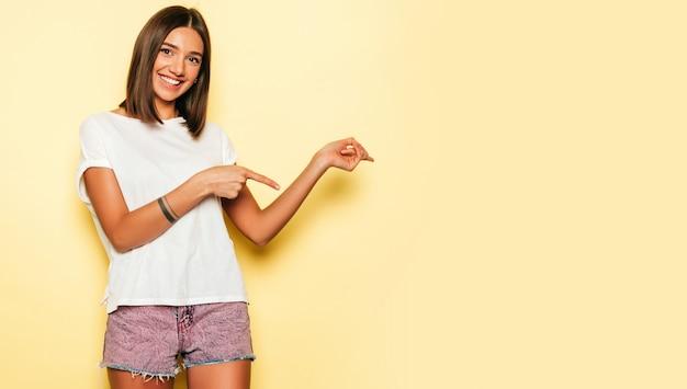 Jovem mulher bonita olhando para a câmera. menina na moda casual verão branco camiseta e jeans shorts. fêmea positiva mostra emoções faciais. modelo apontando com os dedos em uma direção Foto gratuita