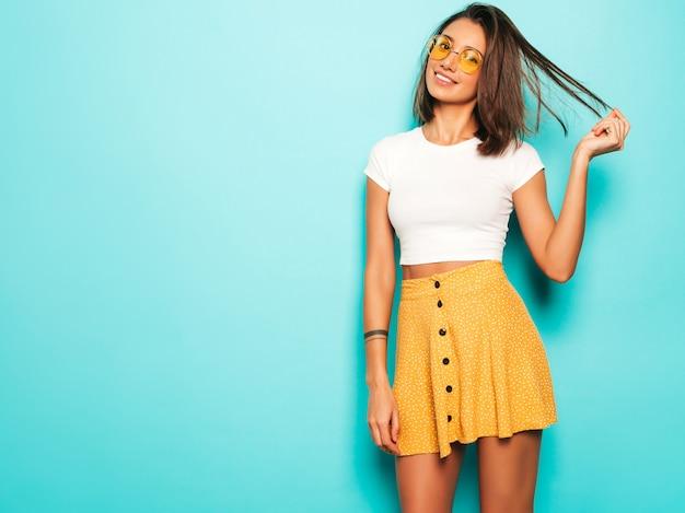 Jovem mulher bonita olhando para a câmera. menina na moda em camiseta casual verão branco e saia amarela em óculos de sol redondos. fêmea positiva mostra emoções faciais. modelo engraçado isolado em azul Foto gratuita
