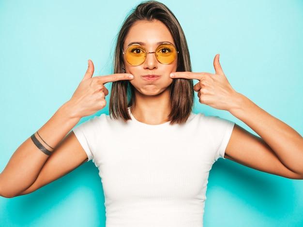 Jovem mulher bonita olhando para a câmera. menina na moda em camiseta casual verão branco e saia amarela em óculos de sol redondos. fêmea positiva mostra emoções faciais. modelo engraçado soprando as bochechas. Foto gratuita