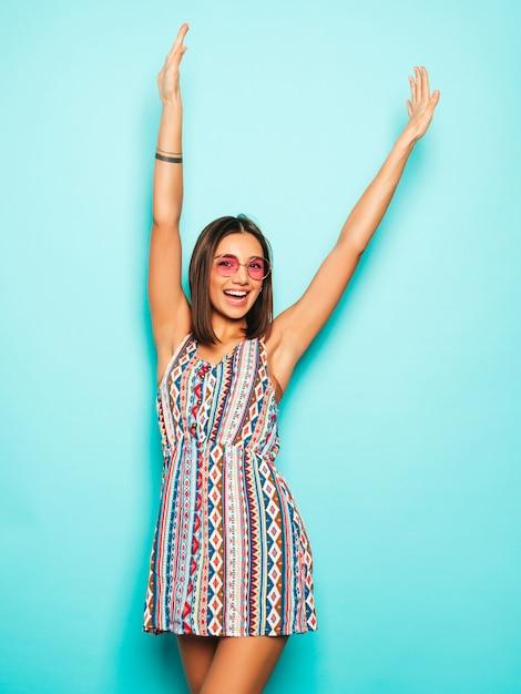 Jovem mulher bonita olhando para a câmera. menina na moda em vestido de verão casual e óculos de sol redondos. fêmea positiva mostra emoções faciais. modelo levantando as mãos e comemorando Foto gratuita