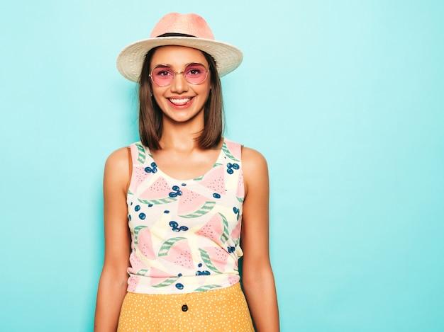 Jovem mulher bonita olhando para a câmera no chapéu. menina na moda em camiseta casual verão branco e saia amarela em óculos de sol redondos. fêmea positiva mostra emoções faciais. modelo engraçado isolado em azul Foto gratuita