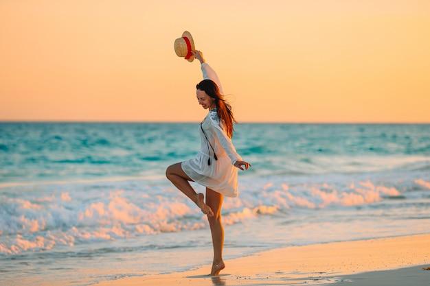 Jovem mulher bonita praia tropical no pôr do sol. Foto Premium