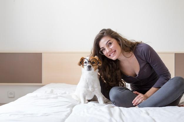 Jovem mulher bonita que encontra-se na cama com seu cão pequeno bonito além. casa, ambiente interno e estilo de vida. eles estão usando óculos hipster Foto Premium