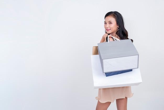 Jovem mulher bonita que guarda sacos de compras com sorriso no fundo branco. Foto Premium