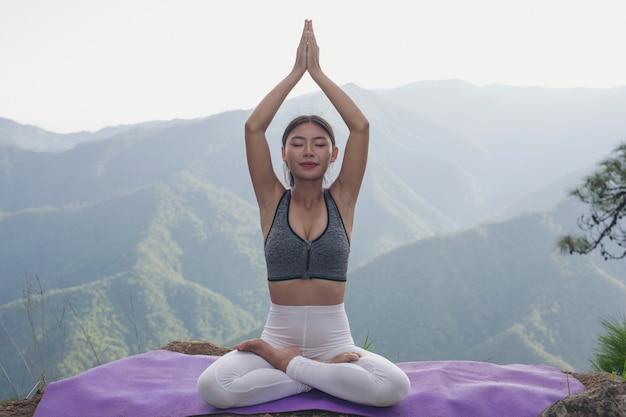 Jovem mulher bonita que medita e que exercita sobre ele. Foto gratuita