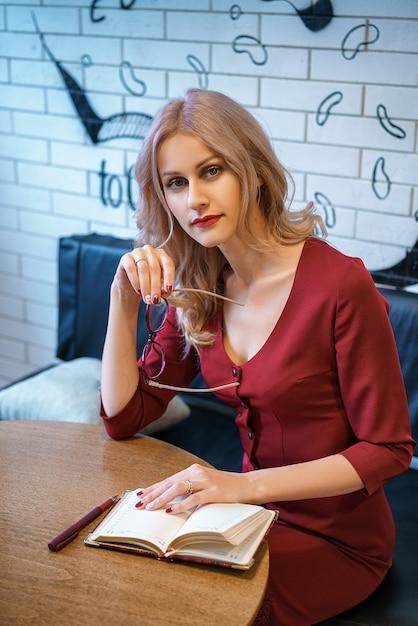 Jovem mulher bonita que senta-se em uma tabela com um caderno e um telefone. Foto Premium