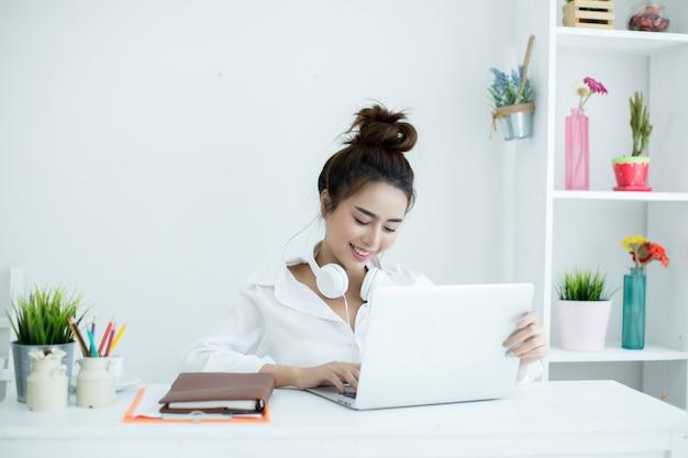 Jovem mulher bonita que trabalha em seu portátil em sua sala. Foto gratuita