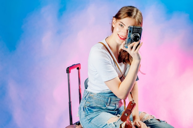 Jovem mulher bonita segurando uma câmera retro vai viajar Foto Premium
