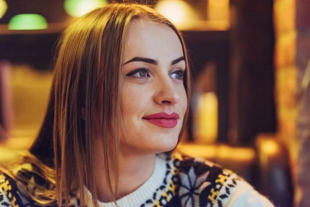 Jovem mulher bonita sentada no café, bebendo café. modelo olhando para cima. natal, ano novo, dia dos namorados, férias de inverno Foto Premium