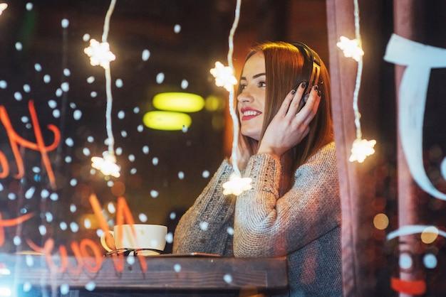 Jovem mulher bonita sentada no café, bebendo café. modelo ouvindo música. natal, ano novo, dia dos namorados, férias de inverno Foto Premium