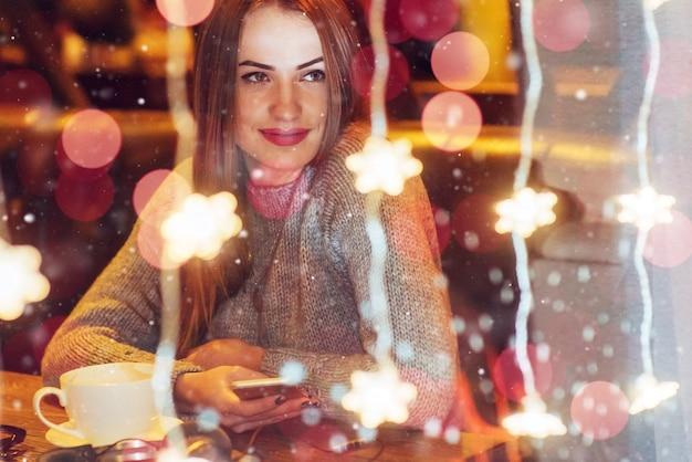 Jovem mulher bonita sentada no café, bebendo café. natal, ano novo, dia dos namorados, férias de inverno Foto Premium