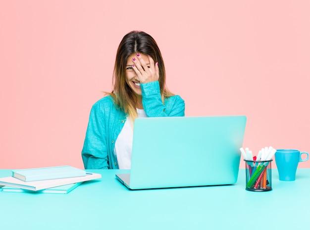 Jovem mulher bonita trabalhando com um laptop rindo e batendo na testa como dizer dãããããããão! eu esqueci ou isso foi um erro estúpido Foto Premium