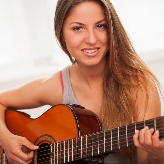 Jovem, mulher bonita, violão jogo Foto gratuita
