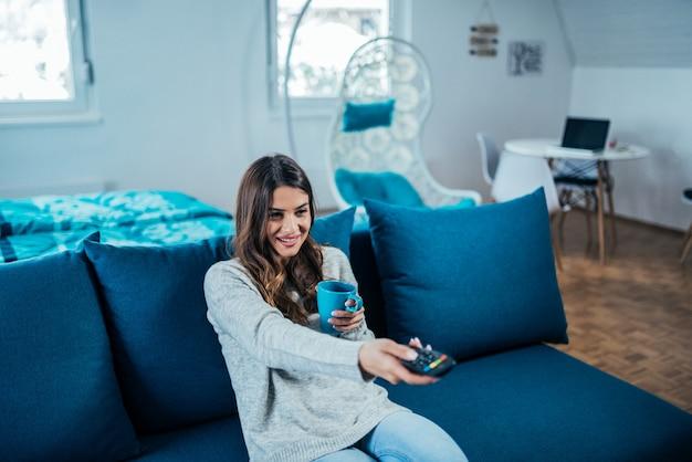 Jovem mulher bonito que olha a tevê. segurando uma caneca e controle remoto enquanto está sentado no sofá. Foto Premium
