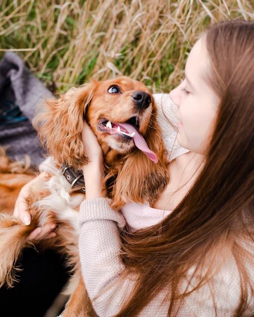 Jovem mulher brincando com seu cachorro Foto gratuita