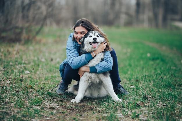 Jovem mulher brincar com cães husky para um passeio na floresta de primavera. rindo se divertindo, feliz com pet Foto Premium