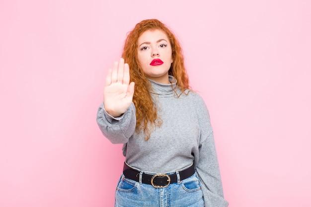 Jovem mulher cabeça vermelha olhando sério, popa, descontente e com raiva mostrando a palma da mão aberta, fazendo o gesto de parada contra a parede rosa Foto Premium