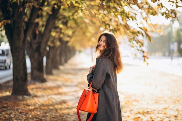 Jovem mulher caminhando em um parque de outono Foto gratuita