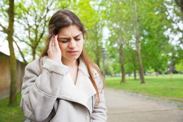 Jovem mulher cansada tocando o templo no parque Foto gratuita