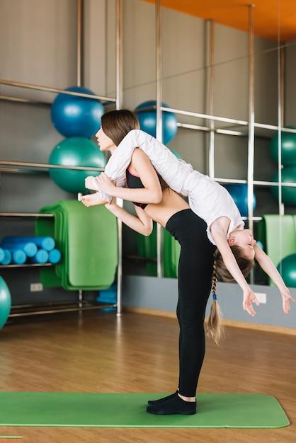 Jovem, mulher, carregar, dela, cute, filha pequena, ligado, costas, durante, exercício Foto gratuita