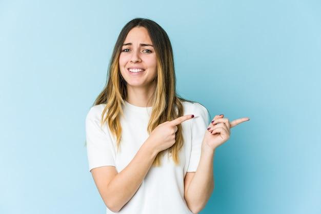 Jovem mulher caucasiana chocada apontando com o dedo indicador para um espaço de cópia. Foto Premium