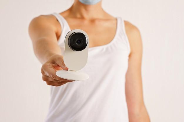 Jovem mulher caucasiana com câmera de segurança e máscara médica facial. triagem de temperatura covid-19 Foto Premium