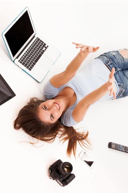 Jovem mulher caucasiana com dispositivos eletrônicos Foto gratuita