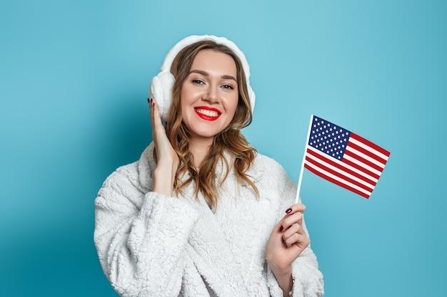 Jovem mulher caucasiana com um casaco de pele branca falsa está sorrindo e segurando uma pequena bandeira americana isolada contra uma parede azul. Foto Premium