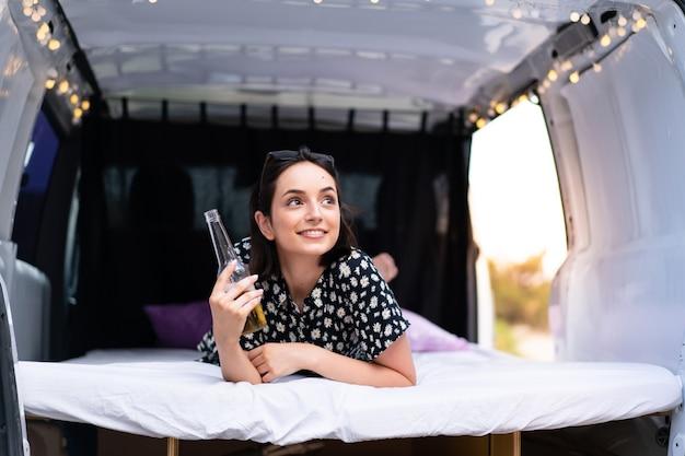 Jovem mulher caucasiana em uma van de camping ao ar livre Foto Premium