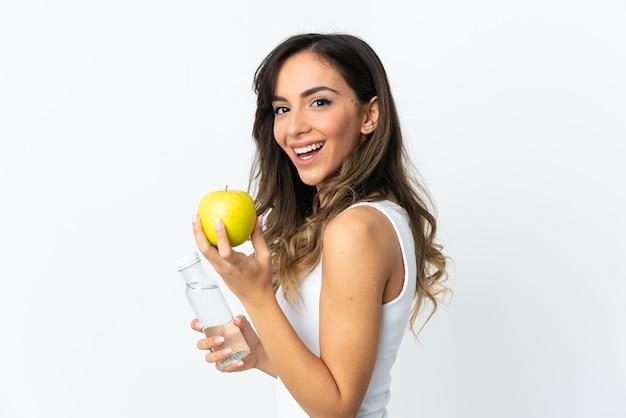 Jovem mulher caucasiana isolada na parede branca com uma maçã e uma garrafa de água Foto Premium